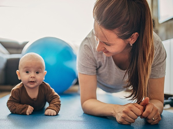 Mother exercising with her baby son at home